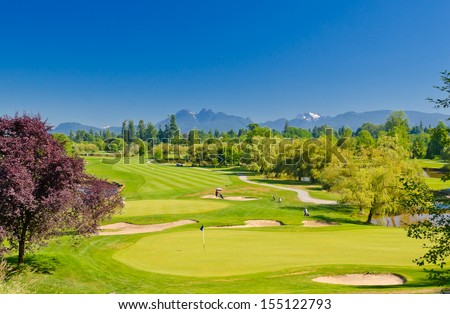 Great view, outlook, panorama at the beautiful golf course with the mountains at the back. Canada, Vancouver. - stock photo