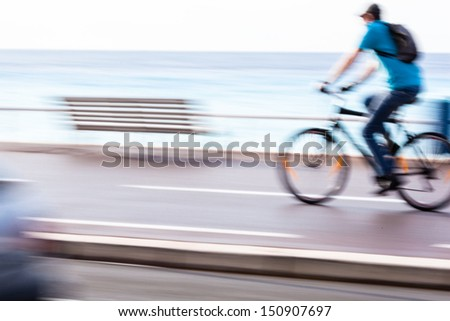 Great way to get around in a city -Motion blurred cyclist going fast on a city bike lane, by the sea shore - stock photo