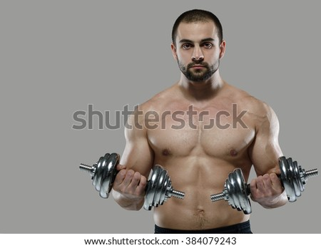 Great workout. Portrait of muscular professional bodybuilder and fitness trainer. Muscular male sportsman is training himself with dumbbells. Gym fitness sport muscle concept. - stock photo