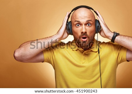 Great young bald man in yellow t-shirt with earphones - stock photo