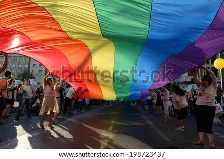 GREECE, Athens JUNE 14, 2014: Participants with the rainbow flag, the symbol of the gay rights movement, during the annual Gay Pride parade event in central Athens, celebrate 10 years of Athens Pride. - stock photo