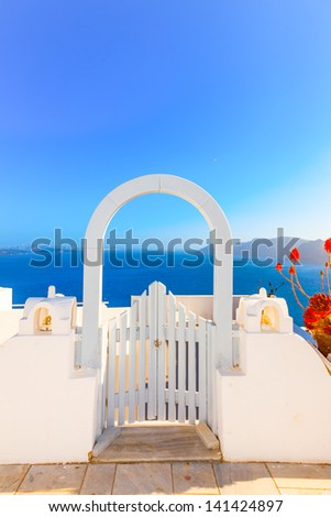 Greece Santorini island in Cyclades, traditional sights of colorful and white washed houses with wooden door frames and caldera sea in background - stock photo