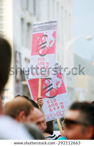 GREECE, Thessaloniki JUNE 29, 2015: Supporters of the NO vote in the upcoming referendum protest holding banners reading OUT OF EURO during a rally around the White Tower in Thessaloniki - stock photo