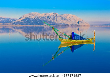 Greece, traditional fishing boat in lake by Mountains at Winter time, Tourlida Greece, Winter - stock photo