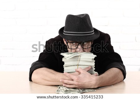 Greediness. emotional man in glasses holding bundles of money. Greed - stock photo