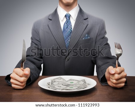 Greedy businessman eating banknotes symbolising consumerism. - stock photo