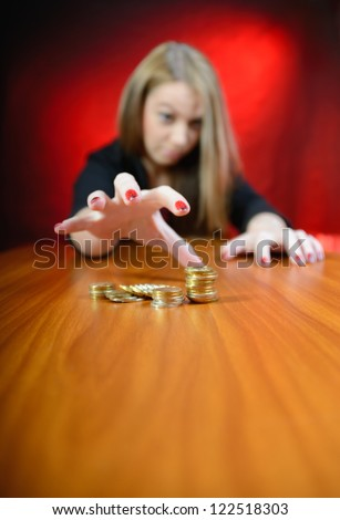Greedy girl gathering coins. Shallow depth of focus - stock photo