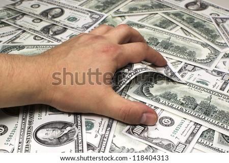 Greedy hand grabbing money - stock photo