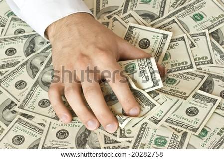 Greedy hand grabs money lot of dollars - stock photo