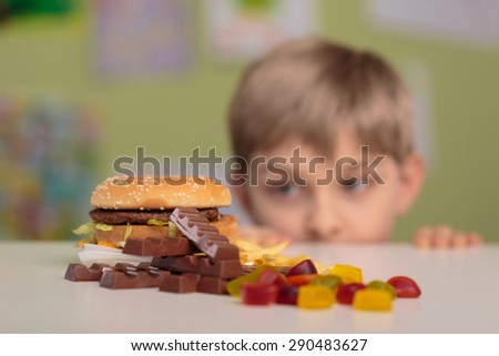 Greedy little boy looking at unhealthy tasty snacks - stock photo
