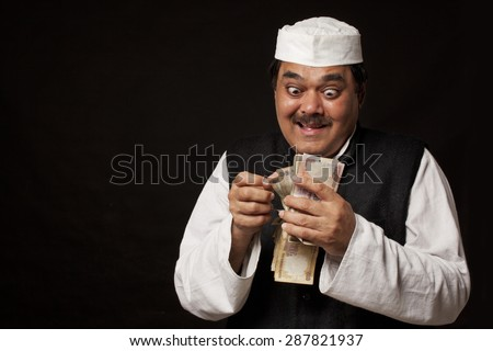 Greedy mature politician counting money over black background - stock photo