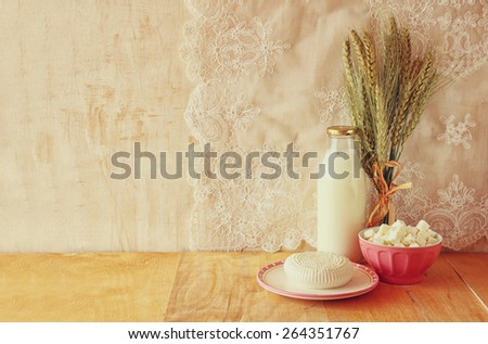 greek cheese , cottage and milk on wooden table over wooden textured background. Symbols of jewish holiday - Shavuot - stock photo