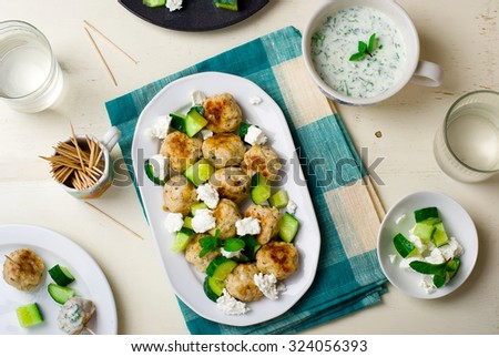 greek chicken meatballs with cucumbers, cheese feta and yogurt sauce. top view, selective focus - stock photo