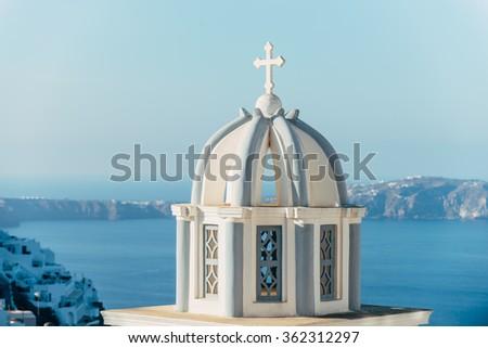 Greek church cupola in Santorini with Caldera view - stock photo