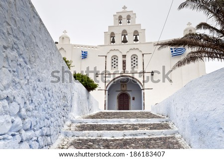 Greek church entrance with bell-tower, national flags in spring day - stock photo