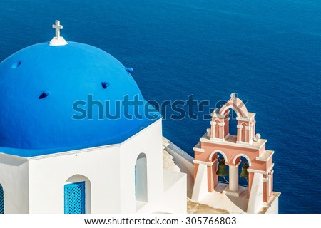 Greek church with blue dome and bell tower near the sea in Oia town, Santorini island, Greece - stock photo