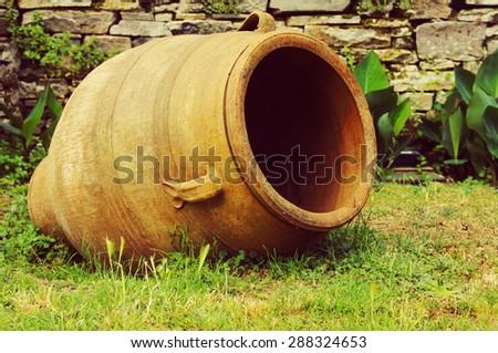 Greek clay amphora on a green grass - stock photo