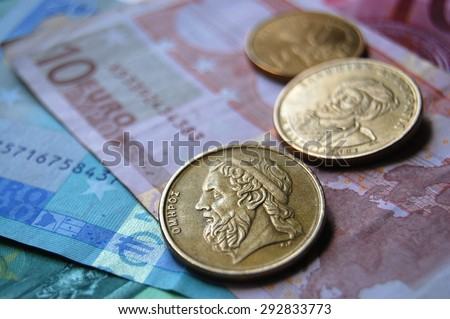 Greek drachma coins on Euro banknotes. Selective focus. Greek epic poet Homer depicted in the old Greek coin - stock photo