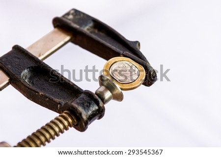 Greek Euro coin squezzed in clamp. Euro crisis.  - stock photo