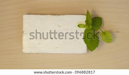Greek feta cheese block isolated on board. - stock photo