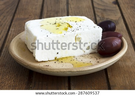 Greek feta cheese, oil, kalamata olives on rustic plate board. - stock photo