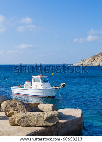 Greek fishing boat in the sea near the pier with a stone ... - stock photo