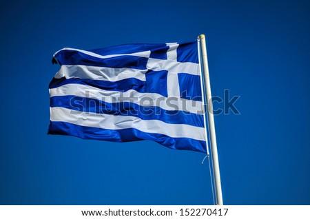Greek flag against blue sky background - stock photo