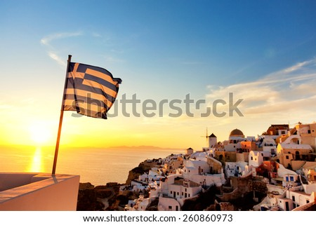 Greek flag waving at sunset in Oia, Santorini, Greece - stock photo