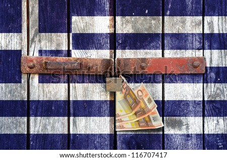 Greek flag with the euro money on the background of old locked doors - stock photo