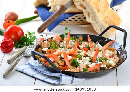 Greek food: Saganaki with shrimps, vegetables and feta cheese - stock photo