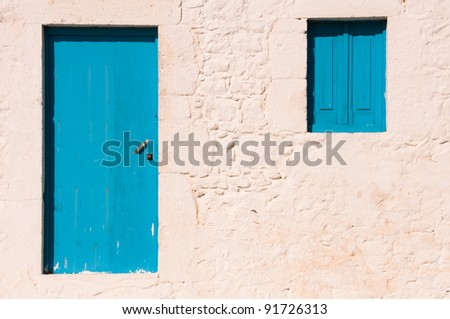 Greek house with blue door and window - stock photo
