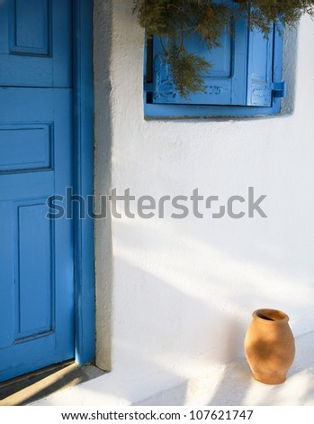 Greek island architecture typical cyclades architecture with small ceramic pot, blue door and shutters. - stock photo