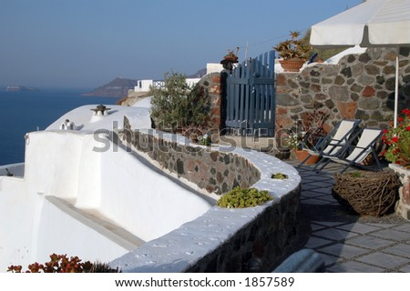 greek island view with lounge chairs on the patio - stock photo