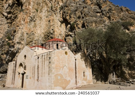 Greek monastery olive tree high rocky wall in the background  - stock photo