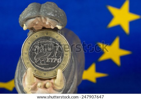 Greek one euro coin in mouth of hippo figurine - stock photo