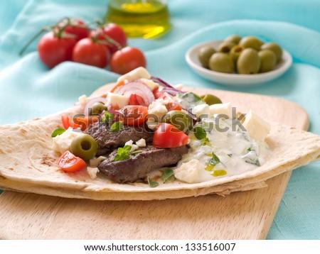 Greek pork souvlaki with pita, tomato and sauce, selective focus - stock photo