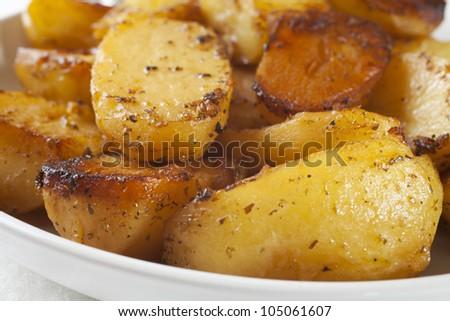 Greek roast potatoes, flavoured with garlic, lemon and oregano. - stock photo