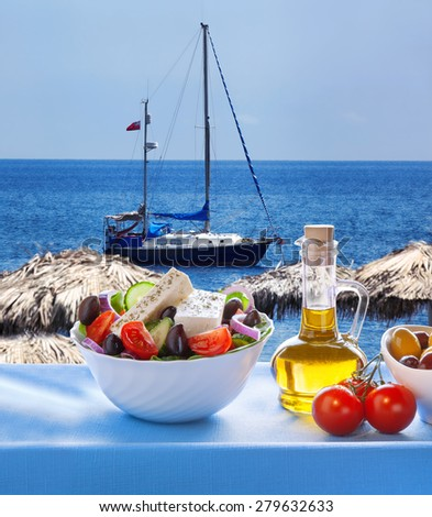 Greek salad against sailboat in Santorini island, Greece - stock photo