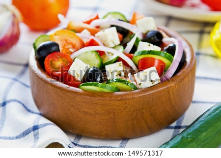 Greek salad in a wood bowl by fresh ingredients - stock photo