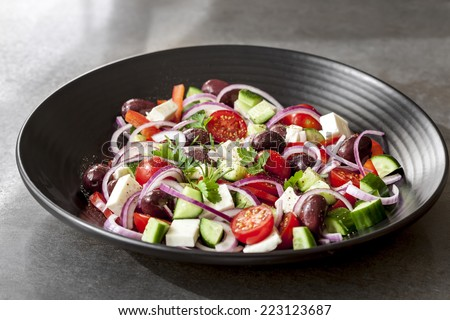 Greek salad in black bowl, over dark slate. - stock photo