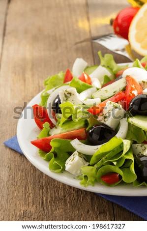 greek salad on wooden background - stock photo