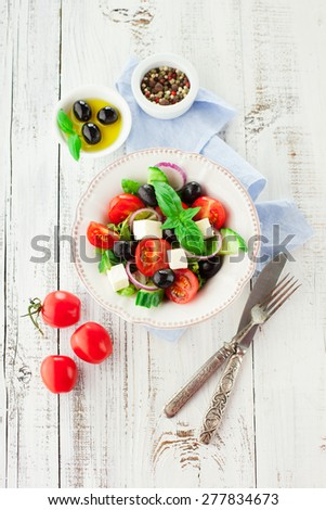 Greek salad with feta cheese, fresh vegetables and olives on rustic white background, top view - stock photo