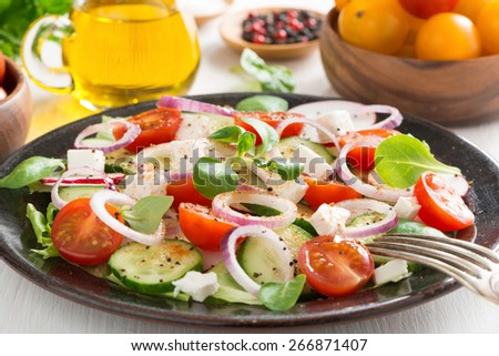 Greek salad with feta cheese on a plate, close-up - stock photo