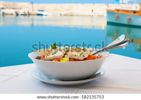 Greek salad with feta cheese on table. Rethymno, Crete, Greece - stock photo