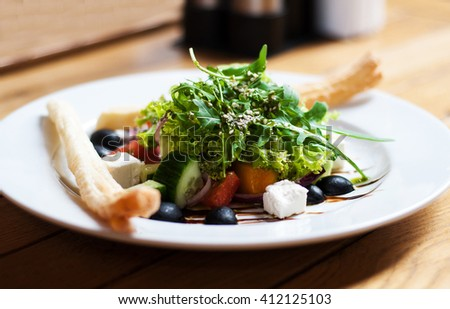 greek salad with fresh vegetables, feta cheese and black olives - stock photo