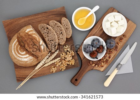Greek snack food with feta cheese, honey, figs, walnuts and pistachio nuts with rye bread and wheat sheaths on maple wood board over grey background.  - stock photo