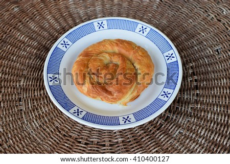 Greek spiral pie traditionally stuffed with cheese, leek or spinach. Vegetarian food appetizer dish. - stock photo