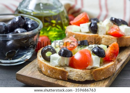 Greek style crostini with feta cheese, tomatoes, cucumber, olives and herbs - stock photo