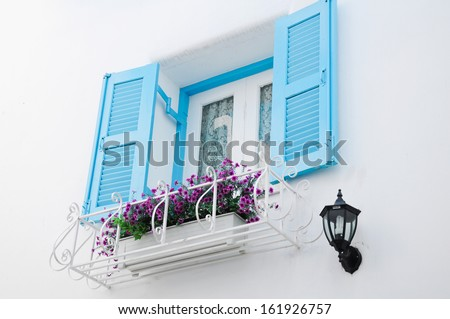Greek Style windows with blue retro wooden shutters on white wal - stock photo