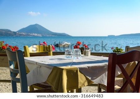 Greek tavern table with colorful wooden chairs by the sea coast. Greece - Gialova with the view of Pylos town in Messinia. - stock photo